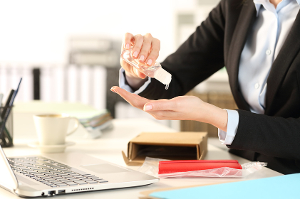 Business woman with opened package sanitizing hands