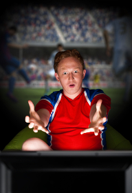 Closeup portrait of young man wearing sportswear fan of football team is watching tv and rooting for his favorite team. Sitting on beanbag alone at night. Light from television.
