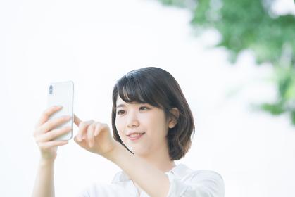 スマホを触る女性(ネット検索・アプリ使う・カメラ撮影)