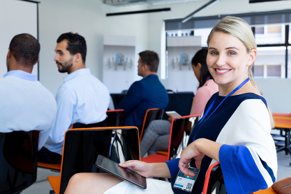 Side view of a Caucasian businesswoman working in a modern office foyer, sitting and turning around, looking to camera and smiling, holding a digital tablet, with coworkers sitting in the background
