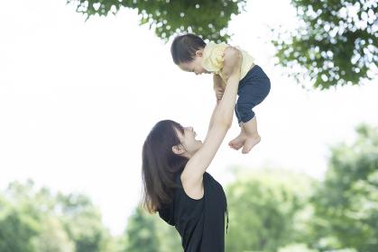 公園で赤ちゃんを抱っこするお母さん
