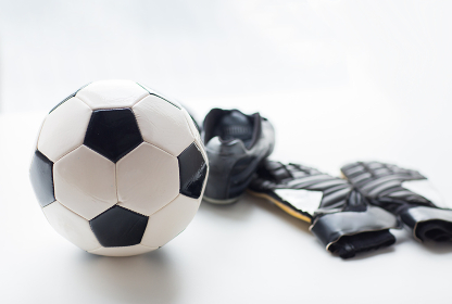 close up of soccer ball, boots and gloves on table