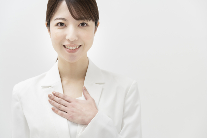 安堵のポーズを取る、白いスーツ姿の女性