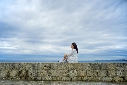 海岸に座って遠くを見つめる日本人女性