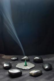 黒い石に囲まれた平たい石の上で焚いているお香