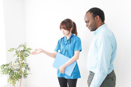 外国人の診察をする若い看護師・新型肺炎・コロナウイルス