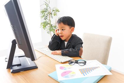 スーツを着て仕事をする子供ビジネスマン