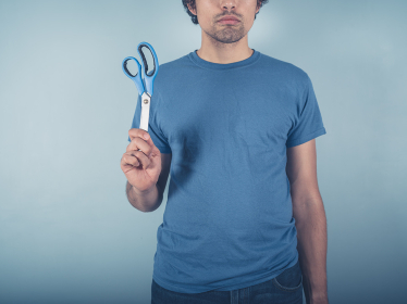A young man wearing a blue t-shirt is holding a pair of scissors