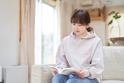 自宅で本を読むアジア人女性