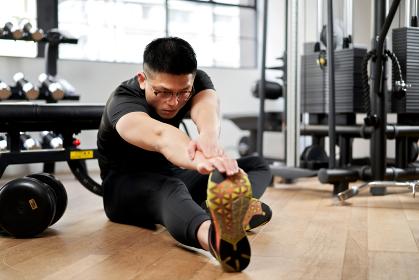 トレーニングジムでストレッチをするアジア人男性