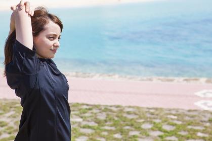 海岸でストレッチをする女性