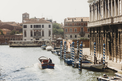Boats on the canal in Venice with houses behind