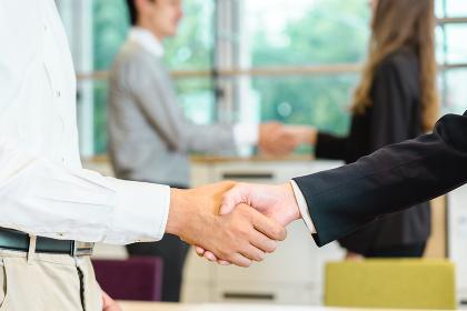 握手をする4人の男性と女性(クローズアップ)