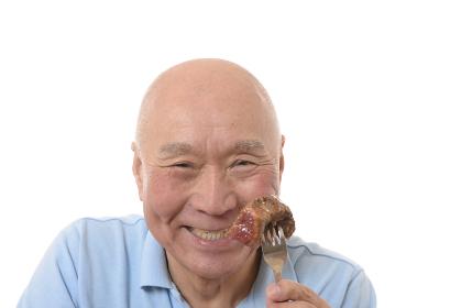 ステーキを食べる日本人シニア