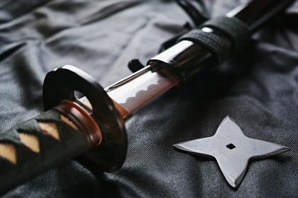 黒い布の上の抜きかけた居合練習刀と手裏剣