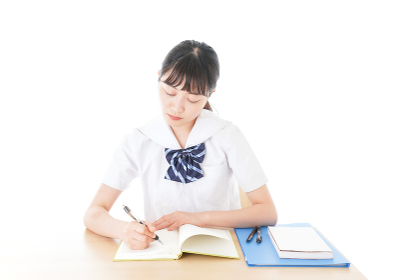 机で勉強をする制服姿の女子学生