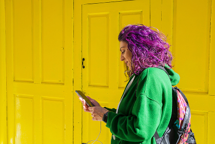 Woman Using Mobile Phone Next To A Yellow Door