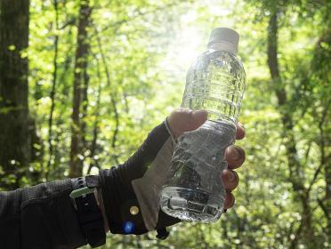 山でミネラルウォーターのペットボトルを持った男性