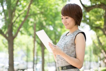 笑顔の女性 タブレットコンピューター 屋外
