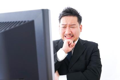 パソコンの前で憤慨するビジネスマン