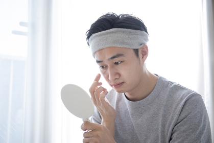 部屋でスキンケアをする若い日本人の男性