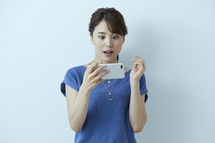 スマートフォンを見て驚く日本人女性