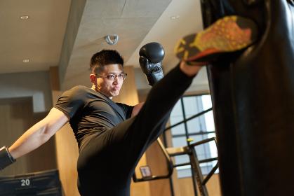 パンチバッグを蹴るアジア人男性