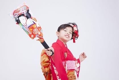 振り袖姿で羽子板を持つ女児