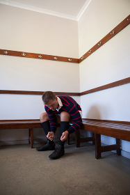Rugby player tying sports shoes while sitting on bench