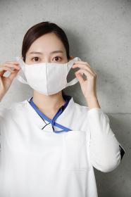 真剣な表情でマスクをつける医療従事者の女性