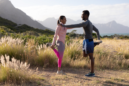Fit african american couple in sportswear stretching in tall grass. healthy lifestyle, exercising in nature.