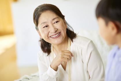 孫とソファでくつろぐ日本人シニア