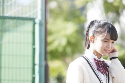 イヤホンで音楽を聴く女子校生