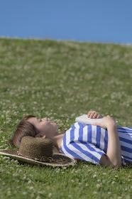 草原で本を持って仰向けに寝る日本人女性
