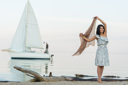 Free woman enjoying freedom feeling happy at beach at morning. Beautiful serene woman and welcoming yacht and sailor with arms opened outstretched up. Hispanic Caucasian female model
