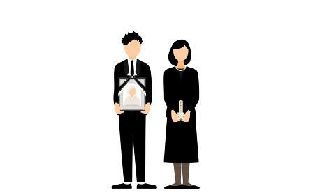 遺影と仮位牌をもって立つ若い夫婦