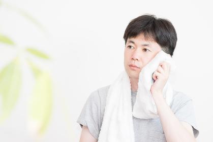 汗を拭く男性(トレーニング・クールダウン・リラックス・健康)