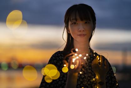 イルミネーションライトを見つめる若い女性