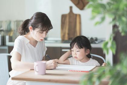 ダイニングテーブルでお絵かきをするお母さんと娘