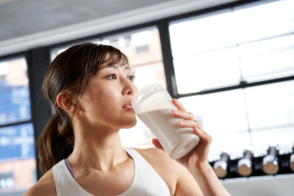 トレーニング後にプロテインを飲むアジア人女性