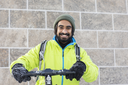 young man with beard outside with  winterjacket and scooter in snow