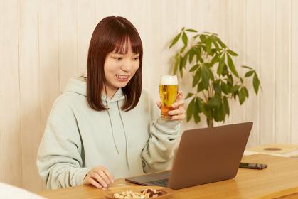 家でビールを飲む若い女性