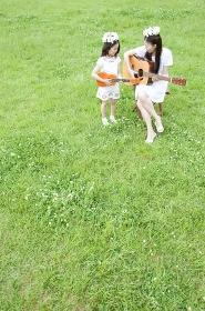 草原で楽器を演奏する女性と女の子