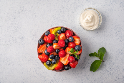 Fresh fruit salad with different ingredients with mint and sour cream. Healthy diet. Copy space for text. Top view