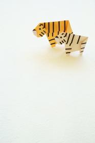 白い背景に折り紙の左を向いた2頭の黄色い虎とホワイトタイガー縦構図