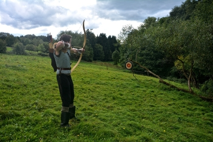 medieval archer,aiming with bow and arrow at straw disc in nature
