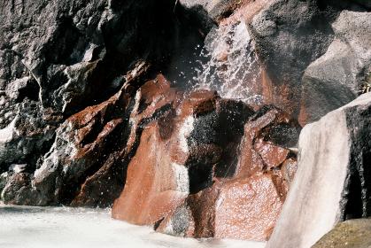 岩石から流れ出す温泉のイメージ