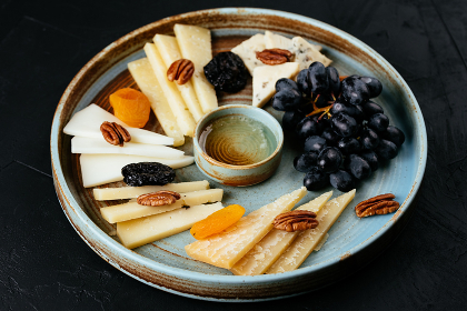 cheese plate with a variety of cheeses on a black background