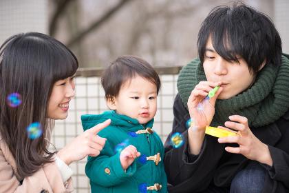 シャボン玉で遊ぶ子供(3人家族)