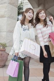 友達とショッピングバッグを持つ笑顔の女性